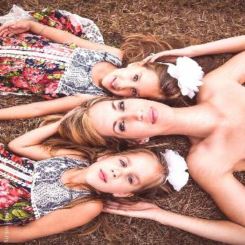 Mother and her twin daughters lying down on the grass by aremafoto | Stocksy United