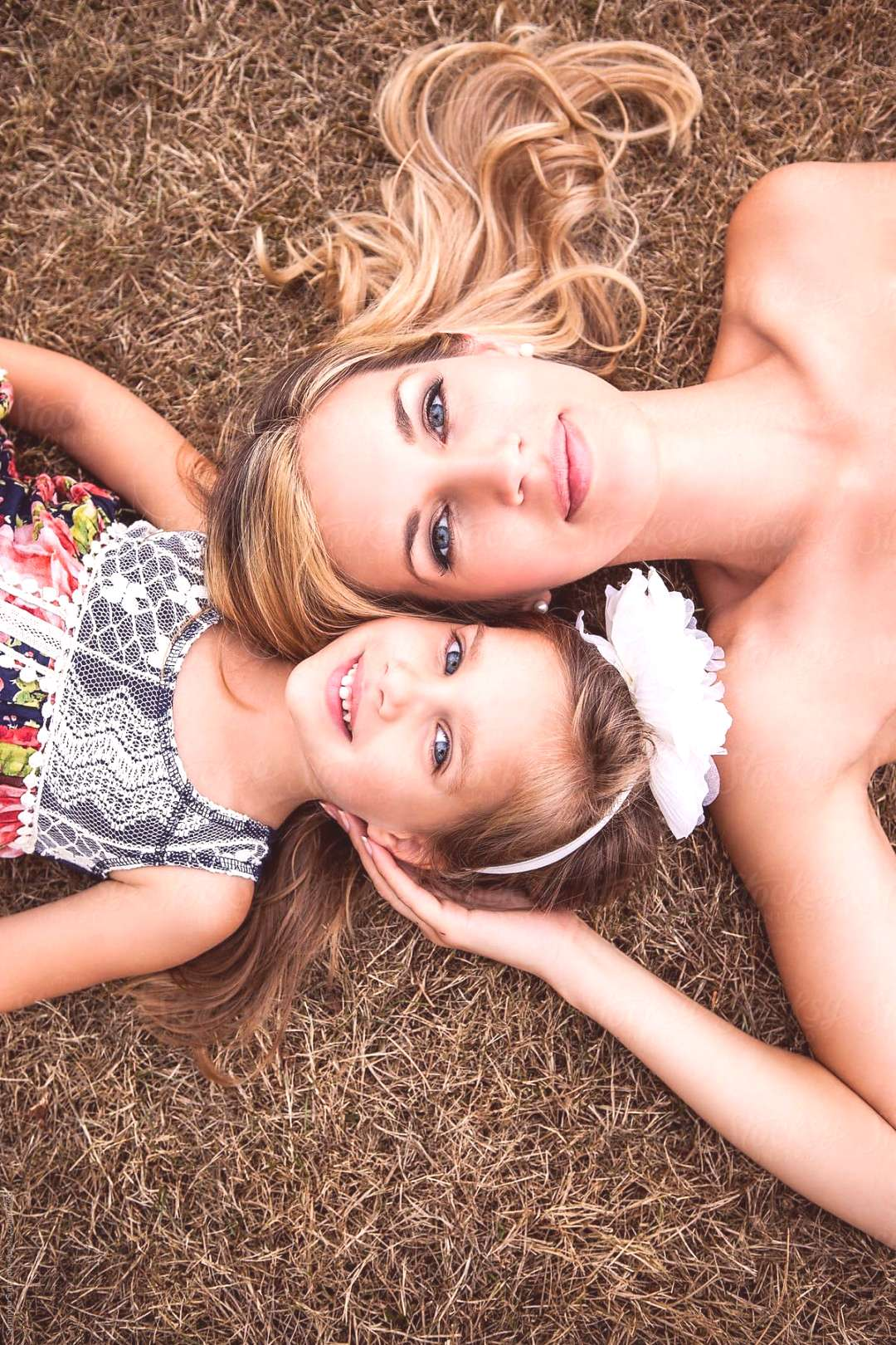 A portrait of a mother and her daughter lying down on the grass
